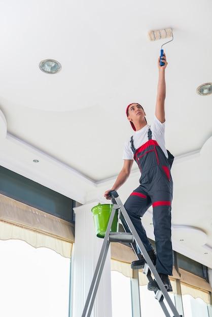 Giovane pittore che dipinge il soffitto nel concetto della costruzione Foto Premium