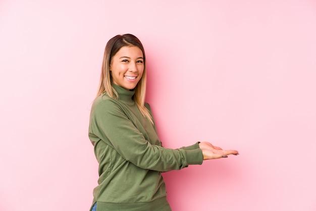 Giovane posa caucasica della donna isolata tenendo uno spazio della copia su una palma. Foto Premium