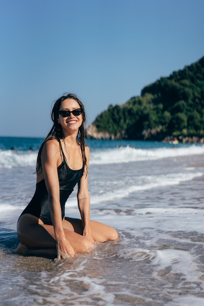 Giovane posa sexy del brunette sulle sue ginocchia nel mare Foto Gratuite