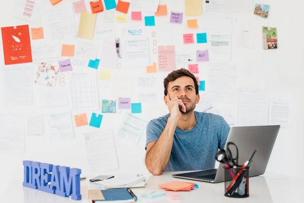 Giovane premuroso che si siede vicino al computer portatile contro la parete con le note Foto Gratuite