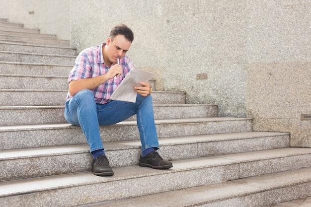 Giovane premuroso serio che cerca il lavoro in giornale Foto Gratuite
