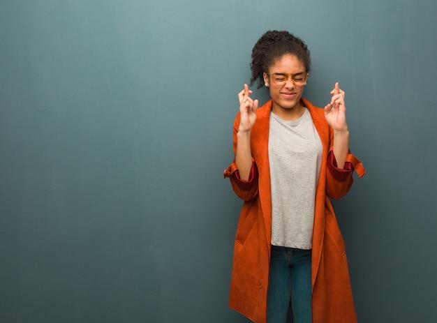 Giovane ragazza afroamericana nera con gli occhi azzurri che attraversano le dita per avere fortuna Foto Premium