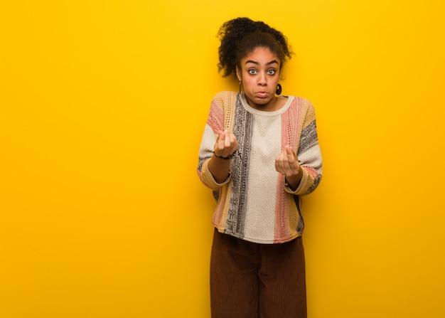 Giovane ragazza afroamericana nera con gli occhi azzurri che fanno un bisogno di gesto Foto Premium