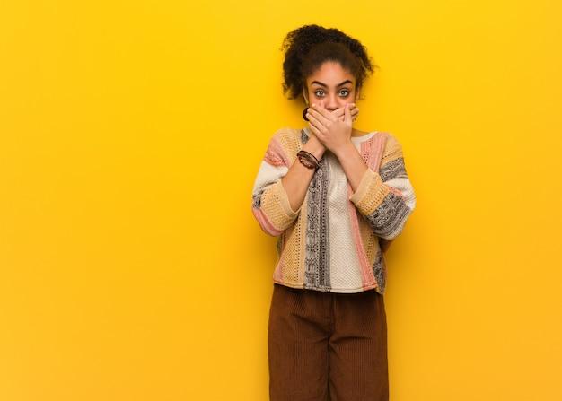 Giovane ragazza afroamericana nera con gli occhi azzurri sorpresa e scioccata Foto Premium