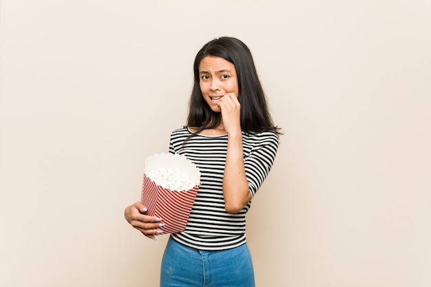 Giovane ragazza asiatica che tiene le unghie mordaci di un secchio del popcorn, nervose e molto ansiose. Foto Premium