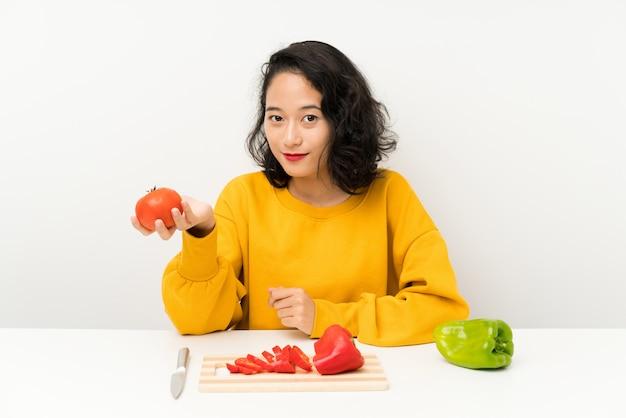 Giovane ragazza asiatica con le verdure in una tabella Foto Premium