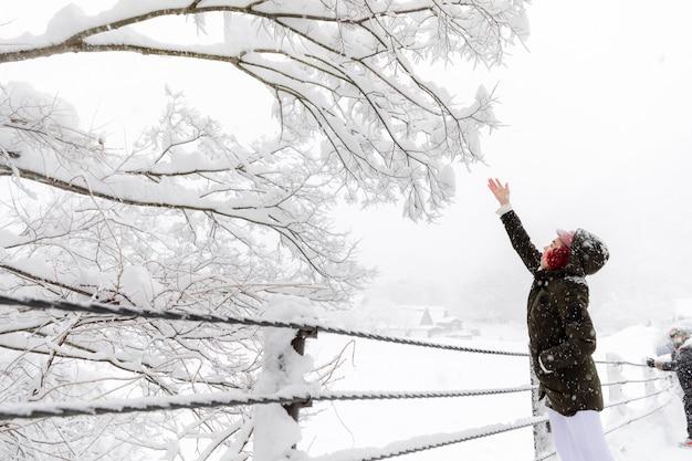 Giovane ragazza asiatica della donna nella stagione di neve di inverno Foto Premium
