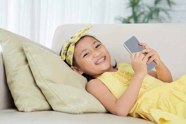 Giovane ragazza asiatica sdraiata sul divano con lo smartphone, guardando la fotocamera e sorridente Foto Gratuite