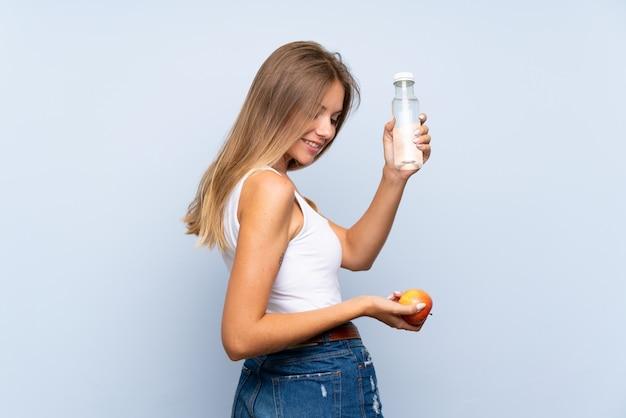 Giovane ragazza bionda con una bottiglia di acqua sopra la parete isolata Foto Premium