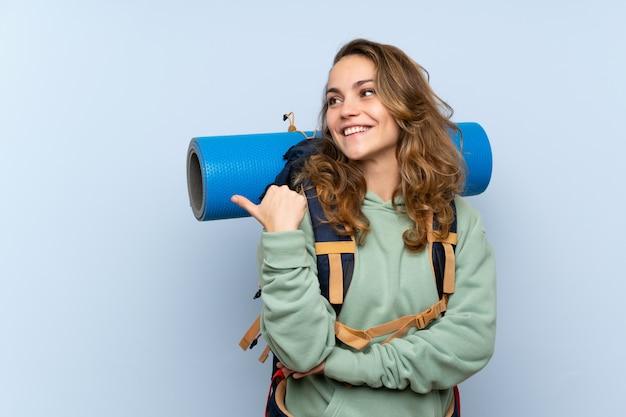 Giovane ragazza bionda della viandante sopra la parete blu isolata che indica il lato per presentare un prodotto Foto Premium