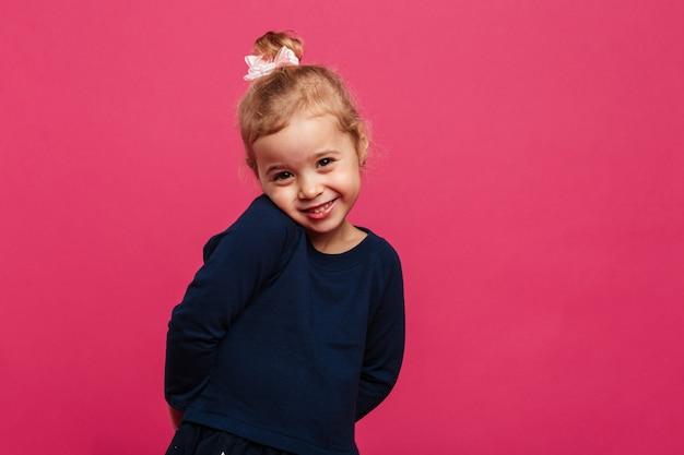Giovane ragazza bionda timida che posa e che esamina la macchina fotografica sopra la parete rosa Foto Gratuite