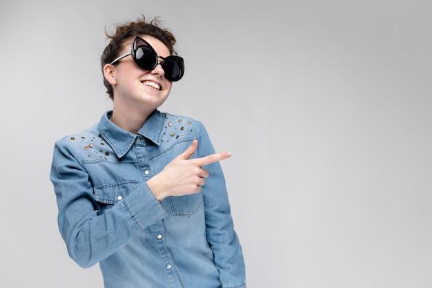 Giovane ragazza bruna con gli occhiali neri. occhiali per gatti. i capelli sono raccolti in una crocchia. ragazza che balla Foto Premium