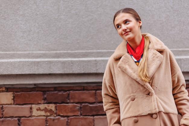 Giovane ragazza carina elegante in una pelliccia passeggiando per la città vicino a case in legno e muri in pietra Foto Premium