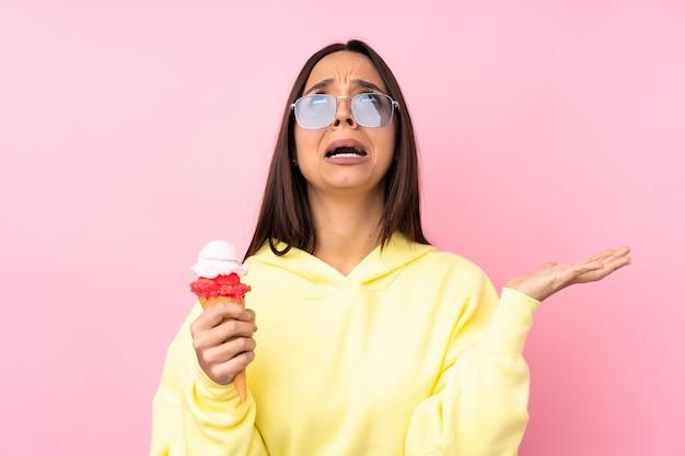 Giovane ragazza castana che tiene un gelato della cornetta sopra il rosa frustrato da una brutta situazione Foto Premium