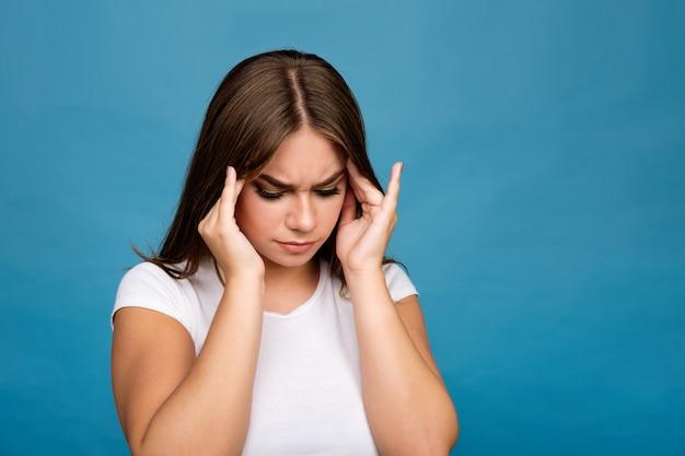 Giovane ragazza castana in maglietta bianca che soffre di un'emicrania, fondo blu Foto Premium