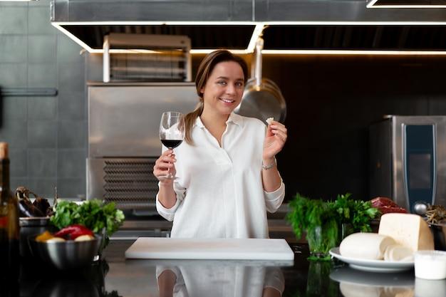 Giovane ragazza caucasica in piedi in cucina in uniforme bianca sorridente e degustazione di vino rosso Foto Premium