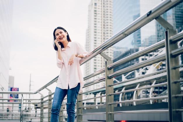 Giovane ragazza chiamata con smartphone e sorriso avendo a parlare all'aperto. concetto di tecnologia. Foto Premium