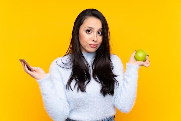 Giovane ragazza colombiana che ha dei dubbi mentre prende una tavoletta di cioccolato in una mano e una mela nell'altra Foto Premium