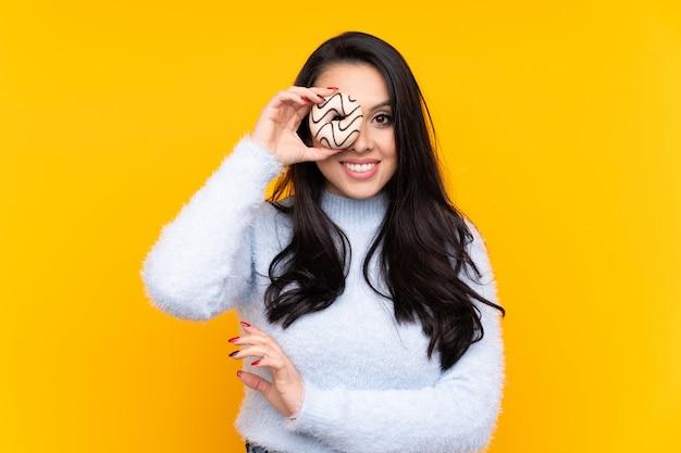 Giovane ragazza colombiana che tiene una ciambella e felice Foto Premium