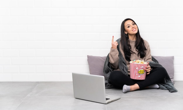 Giovane ragazza colombiana che tiene una ciotola di popcorn e che mostra un film in un computer portatile che indica una grande idea Foto Premium