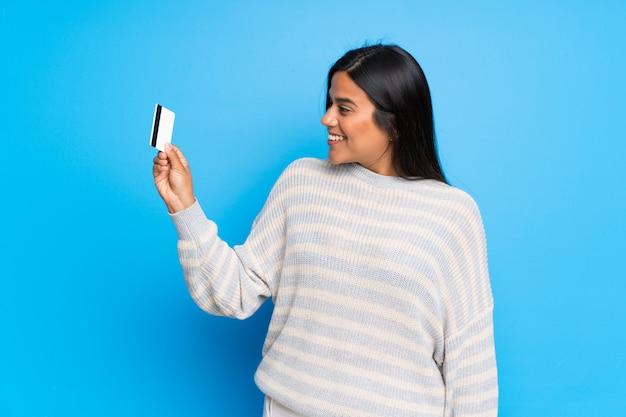 Giovane ragazza colombiana con maglione in possesso di una carta di credito e di pensare Foto Premium