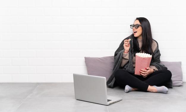 Giovane ragazza colombiana in una stanza con gli occhiali 3d e in possesso di un grande secchio di popcorn Foto Premium