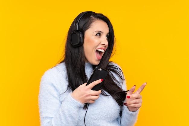 Giovane ragazza colombiana sul muro giallo ascoltando musica con un cellulare e cantando Foto Premium