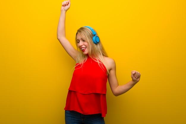Giovane ragazza con abito rosso sulla parete gialla ascoltando musica con le cuffie e ballare Foto Premium