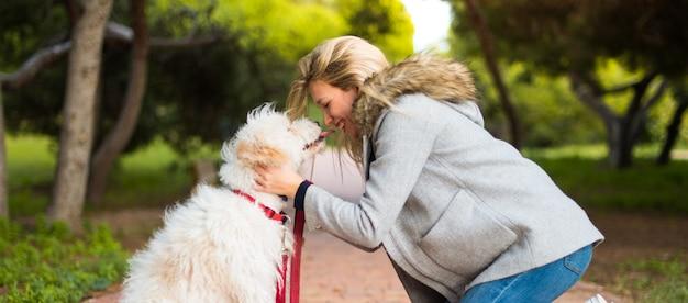 Giovane ragazza con il suo cane in un parco Foto Premium