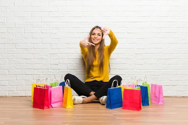 Giovane ragazza con un sacco di borse per la spesa messa a fuoco faccia. Foto Premium