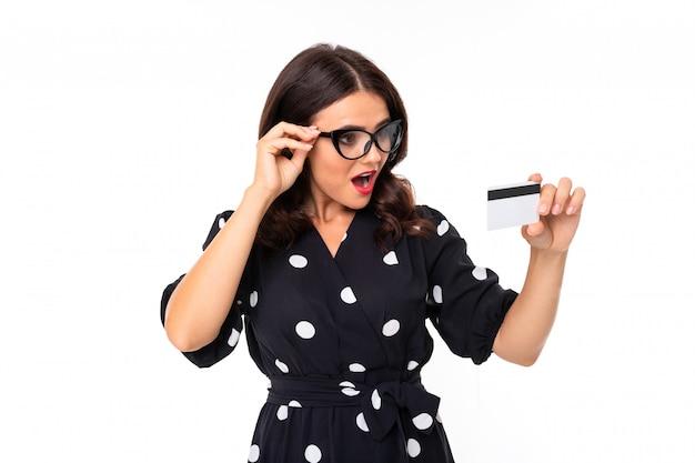 Giovane ragazza con un sorriso delizioso, denti piatti, rossetto rosso, lunghi capelli castani ondulati, bel trucco, occhiali, vestito in bianco e nero in piselli tiene una carta Foto Premium