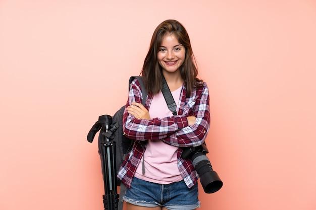 Giovane ragazza del fotografo sopra la risata rosa isolata della parete Foto Premium