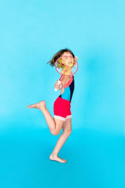 Giovane ragazza dell'adolescente che salta e che gioca volano sulla parete blu Foto Premium