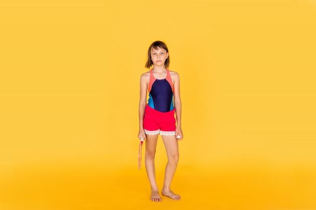 Giovane ragazza dell'adolescente che salta e che gioca volano sulla parete gialla Foto Premium