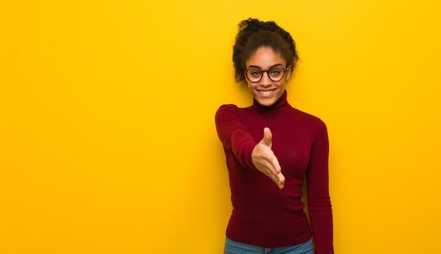 Giovane ragazza dell'afroamericano nero con gli occhi azzurri che raggiungono fuori per accogliere qualcuno Foto Premium