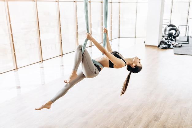 Giovane ragazza di forma fisica del corpo abbastanza esile che pratica yoga della mosca nella palestra. Foto Premium
