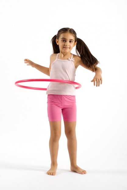 Giovane ragazza graziosa che gioca il cerchio di hula Foto Premium