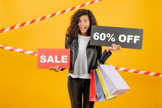 Giovane ragazza nera d'avanguardia con il segno del 60% di vendita e sacchetti della spesa variopinti isolati sopra giallo con nastro adesivo Foto Premium