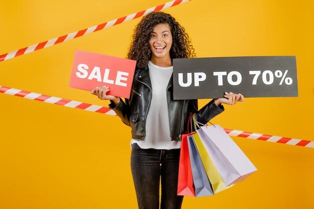 Giovane ragazza nera d'avanguardia con il segno del 70% di vendita e sacchetti della spesa variopinti isolati sopra giallo con nastro adesivo Foto Premium