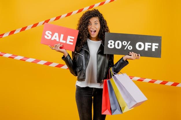 Giovane ragazza nera d'avanguardia con il segno dell'80% di vendita e sacchetti della spesa variopinti isolati sopra giallo con nastro adesivo Foto Premium