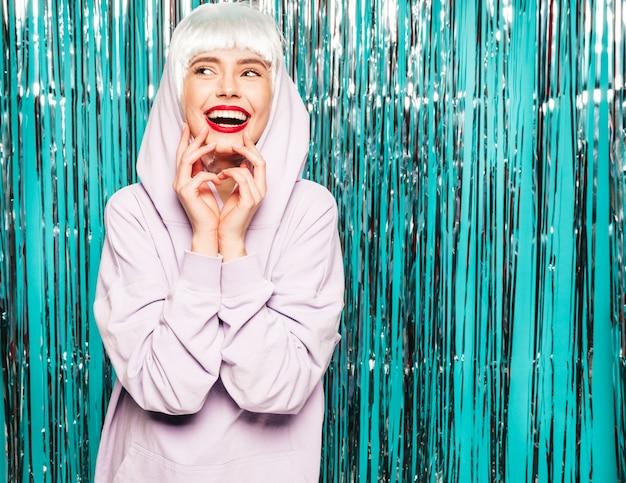 Giovane ragazza sorridente sexy dei pantaloni a vita bassa in parrucca bianca e labbra rosse. bella donna d'avanguardia in vestiti di estate. impazzendo Foto Gratuite