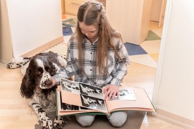 Giovane ragazza sveglia che guarda l'album di foto con il suo cane a casa sul pavimento. Foto Premium