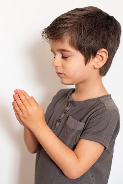 Giovane ragazzo adorabile che prega a casa Foto Gratuite