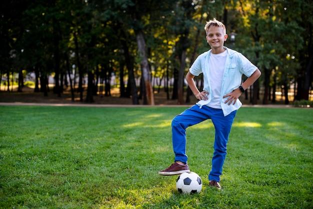 Giovane ragazzo all'aperto con la palla di calcio Foto Gratuite