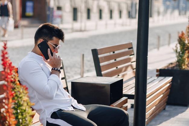 Giovane ragazzo alla moda in camicia con il telefono sul banco in giornata di sole all'aperto Foto Gratuite