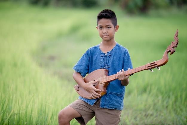 Giovane ragazzo asiatico con la chitarra fatta a mano all'aperto, paese di vita Foto Gratuite