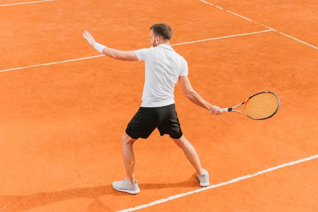 Giovane ragazzo atletico che gioca a tennis Foto Gratuite