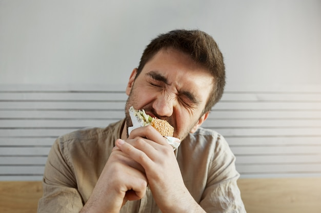 Giovane ragazzo bello con la barba lunga con capelli scuri che mangia panino in fast food con gli occhi chiusi, con espressione felice e soddisfatta. Foto Gratuite