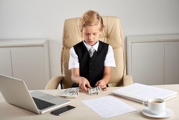 Giovane ragazzo caucasico che si siede nella sedia esecutiva in ufficio e che conta i dollari sullo scrittorio Foto Gratuite