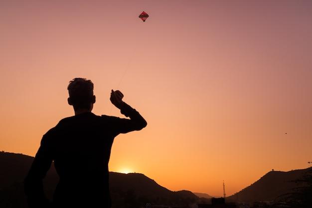 Giovane ragazzo che gioca con l'aquilone al tramonto. retroilluminazione, cielo colorato, vista posteriore, rajasthan, india. Foto Premium